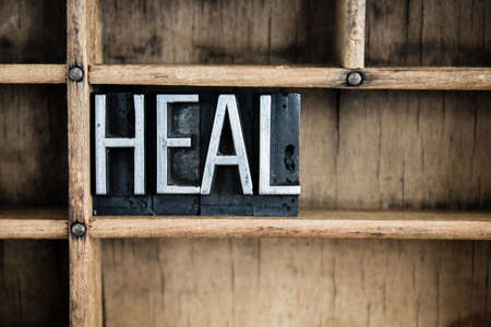 The word HEAL written in vintage metal letterpress type in a wooden drawer with dividers. Stock fotó