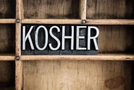 The word KOSHER written in vintage metal letterpress type in a wooden drawer with dividers.
