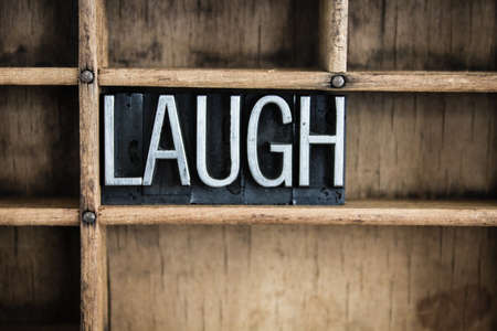 chuckle: The word LAUGH written in vintage metal letterpress type in a wooden drawer with dividers. Stock Photo