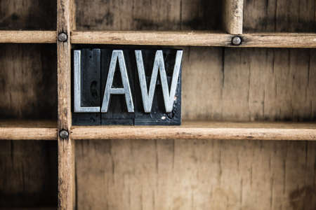proclamation: The word LAW written in vintage metal letterpress type in a wooden drawer with dividers.