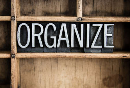obsessive compulsive: The word ORGANIZE written in vintage metal letterpress type in a wooden drawer with dividers.