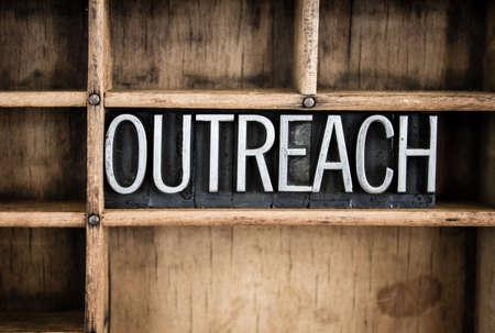 """Das Wort """"OUTREACH"""" im Vintage-Metall-Buch-Typ in einem hölzernen Schublade mit Trennwänden geschrieben."""