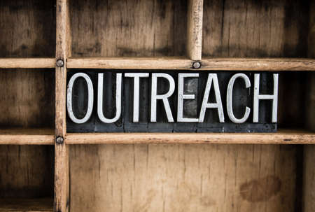 The word OUTREACH written in vintage metal letterpress type in a wooden drawer with dividers.