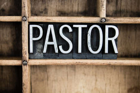 The word PASTOR written in vintage metal letterpress type in a wooden drawer with dividers.