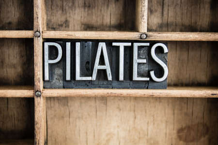 The word PILATES written in vintage metal letterpress type in a wooden drawer with dividers. Stock Photo