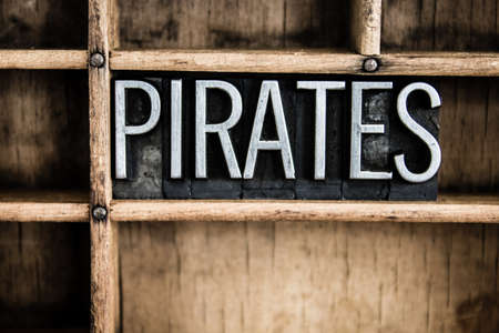 privateer: The word PIRATES written in vintage metal letterpress type in a wooden drawer with dividers.