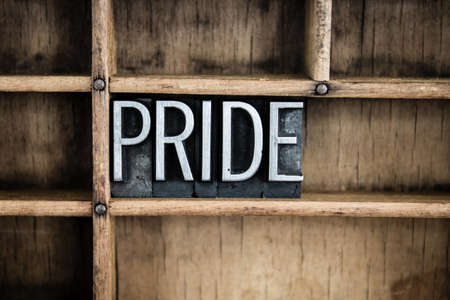 self worth: The word PRIDE written in vintage metal letterpress type in a wooden drawer with dividers. Stock Photo