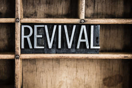 The word REVIVAL written in vintage metal letterpress type in a wooden drawer with dividers.