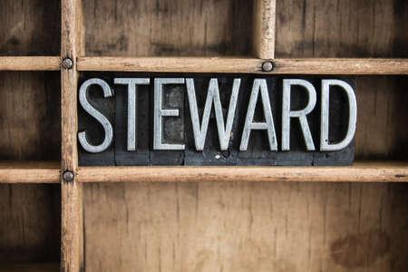 単語「スチュワード」仕切り付き木製引き出し中ヴィンテージの金属活版型で書かれました。 写真素材