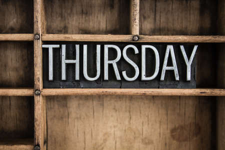 thursday: The word THURSDAY written in vintage metal letterpress type in a wooden drawer with dividers. Stock Photo