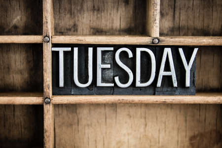 The word TUESDAY written in vintage metal letterpress type in a wooden drawer with dividers. Stock Photo