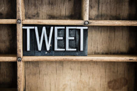 The word TWEET written in vintage metal letterpress type in a wooden drawer with dividers.