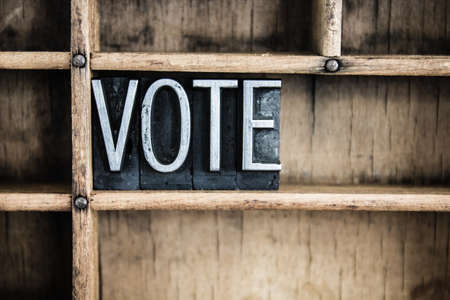 voting booth: The word VOTE written in vintage metal letterpress type in a wooden drawer with dividers. Stock Photo