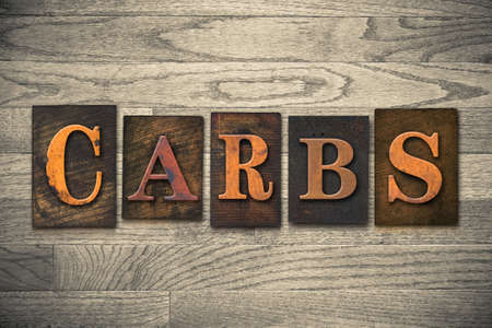 carbs: The word CARBS theme written in vintage, ink stained, wooden letterpress type on a wood grained background.