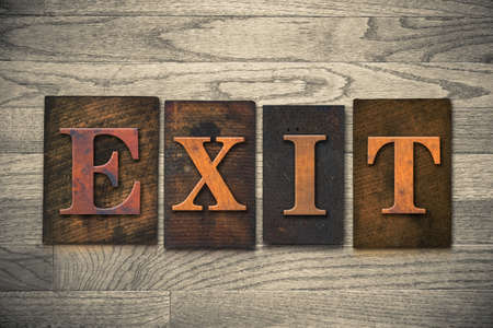 evacuate: The word EXIT theme written in vintage, ink stained, wooden letterpress type on a wood grained background.