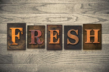 unblemished: The word FRESH theme written in vintage, ink stained, wooden letterpress type on a wood grained background. Stock Photo