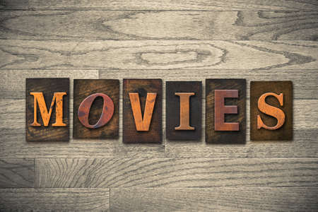 feature films: The word MOVIES theme written in vintage, ink stained, wooden letterpress type on a wood grained background.