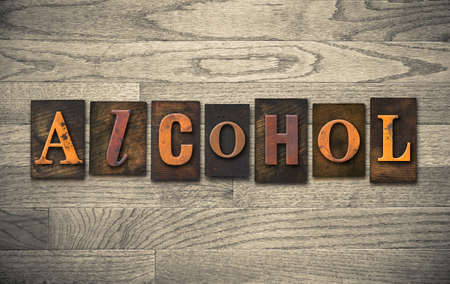 The word ALCOHOL theme written in vintage, ink stained, wooden letterpress type on a wood grained background. photo
