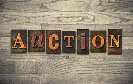 The word AUCTION theme written in vintage, ink stained, wooden letterpress type on a wood grained background.