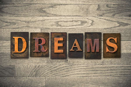 The word DREAMS theme written in vintage, ink stained, wooden letterpress type on a wood grained background. Stock Photo