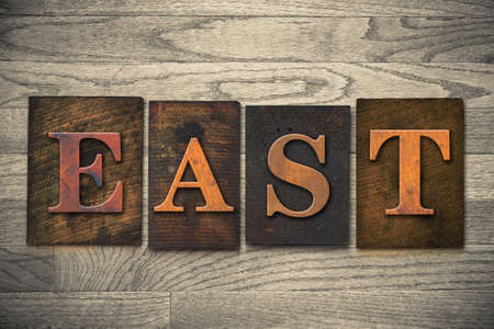 eastward: The word EAST theme written in vintage, ink stained, wooden letterpress type on a wood grained background.