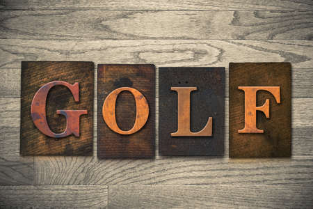The word GOLF theme written in vintage, ink stained, wooden letterpress type on a wood grained background. photo