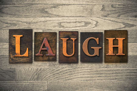 chuckle: The word LAUGH theme written in vintage, ink stained, wooden letterpress type on a wood grained background.