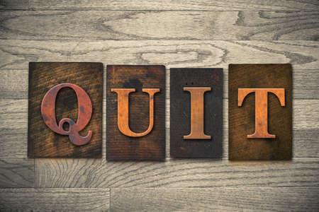 """cease: La parola """"QUIT"""" tema scritto in epoca, di inchiostro colorato, letterpress tipo di legno su un legno a grana di fondo."""