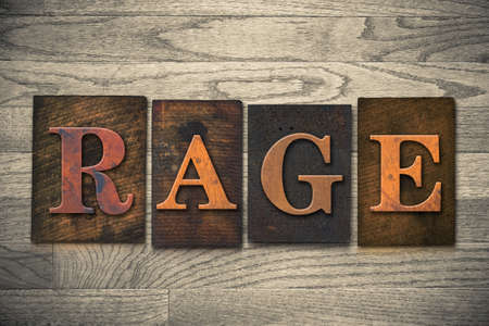 rage: The word RAGE theme written in vintage, ink stained, wooden letterpress type on a wood grained background.