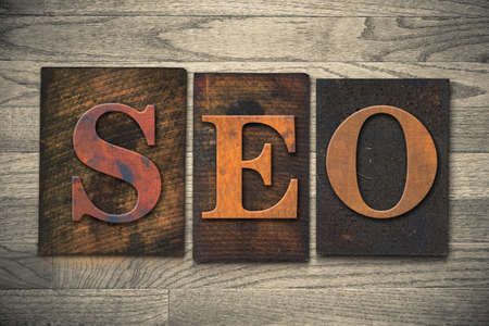 keywords link: The word SEO theme written in vintage, ink stained, wooden letterpress type on a wood grained background. Stock Photo