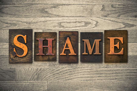 disgraceful: The word SHAME theme written in vintage, ink stained, wooden letterpress type on a wood grained background.