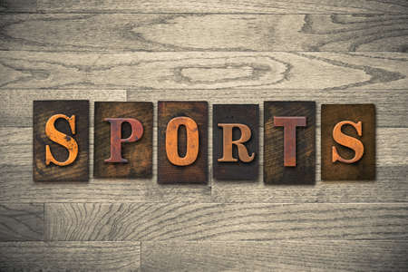 athletic type: The word SPORTS theme written in vintage, ink stained, wooden letterpress type on a wood grained background. Stock Photo