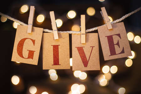 give out: The word GIVE spelled out on clothespin clipped cards in front of glowing lights.