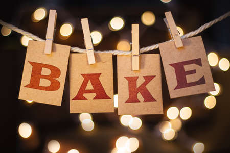 bake sale: The word BAKE printed on clothespin clipped cards in front of glowing lights.
