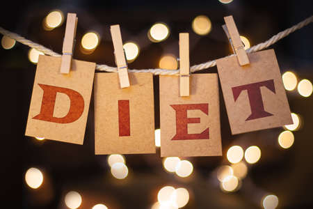fat concept: The word DIET printed on clothespin clipped cards in front of defocused glowing lights. Stock Photo