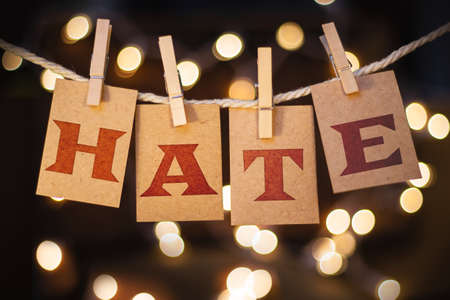 The word HATE printed on clothespin clipped cards in front of defocused glowing lights.