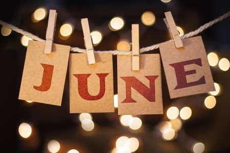 Het woord juni gedrukt op wasknijper geknipt kaarten voor defocused gloeiende lichten. Stockfoto
