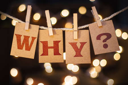 The word WHY? printed on clothespin clipped cards in front of defocused glowing lights. photo