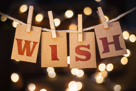 wish desire: The word WISH printed on clothespin clipped cards in front of defocused glowing lights.