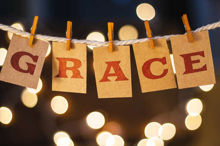 The word GRACE printed on clothespin clipped cards in front of defocused glowing lights.
