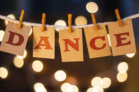 clothespin에 인쇄 된 DANCE라는 단어는 defocused 빛나는 조명 앞에 카드를 잘라 냈습니다. 스톡 콘텐츠