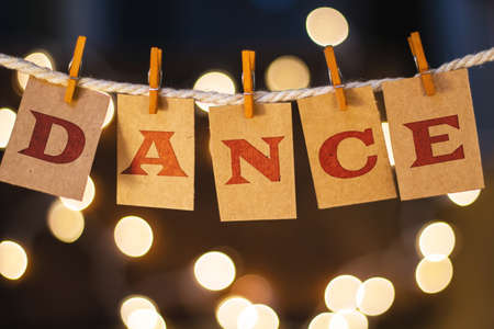tap dance: The word DANCE printed on clothespin clipped cards in front of defocused glowing lights.
