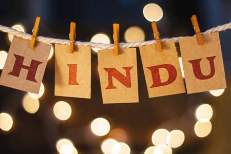 clothespin: The word HINDU printed on clothespin clipped cards in front of defocused glowing lights. Stock Photo