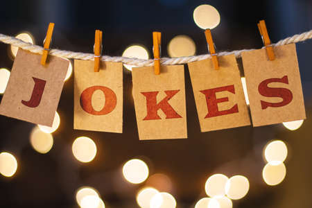 jokes: The word JOKES printed on clothespin clipped cards in front of defocused glowing lights. Stock Photo