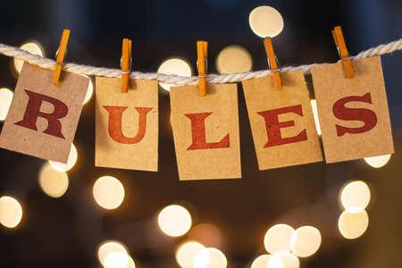 edicto: La palabra REGLAS impresas en clothespin recortan las tarjetas frente a las luces brillantes desenfocado.