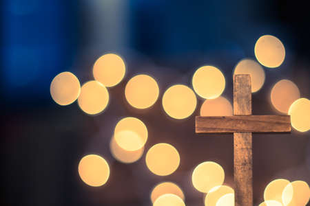 A wooden cross with defocused warm lights in the background.