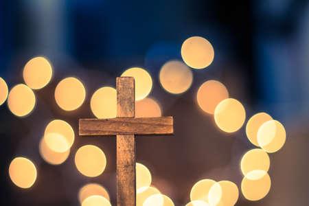 Ein hölzernes Kreuz mit defocused warmen Lichter in den Hintergrund.