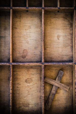 A wooden cross in a vintage wooden letterpress drawer. Stock Photo