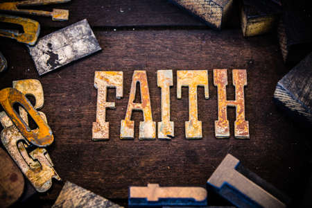 letterpress letters: The word faith written in rusted metal letters surrounded by vintage wooden and metal letterpress type. Stock Photo