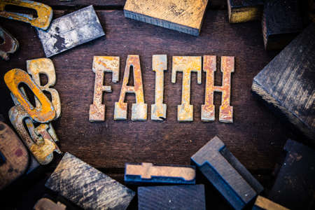 letterpress letters: The word FAITH written in rusted metal letters surrounded by vintage wooden and metal letterpress type.